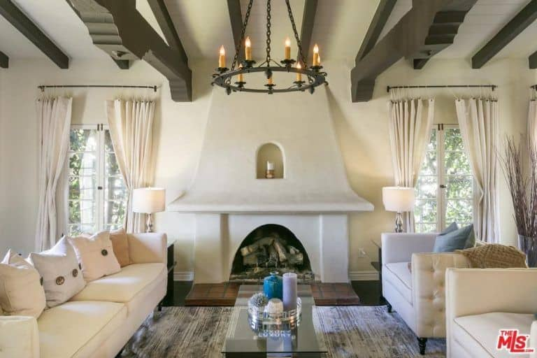 The elegant living room boasts a candle light chandelier and a ceiling with beams along with a traditional fireplace.