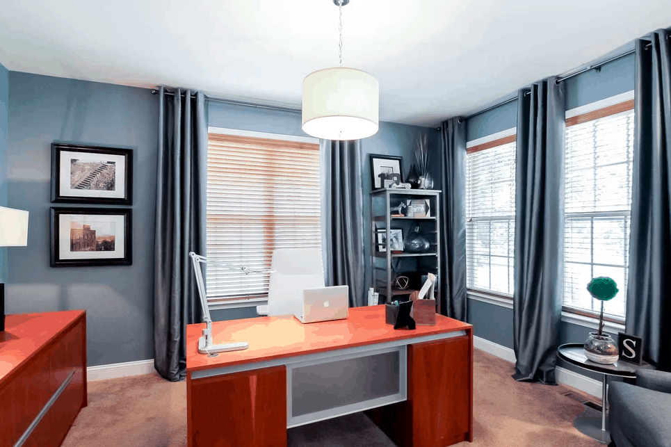 Modern And Contemporary Home Office With Blue Walls And Carpet Flooring  Along With Cherry Finished Table And Pendant Light.