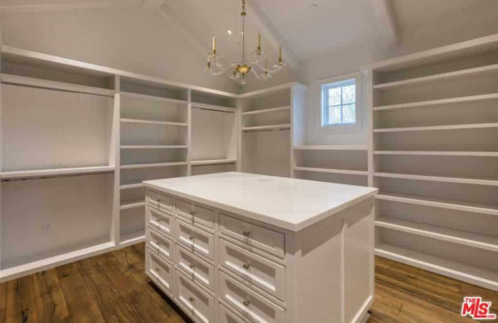 Pure White Closet With Chandelier Lighting And Table Cabinet.