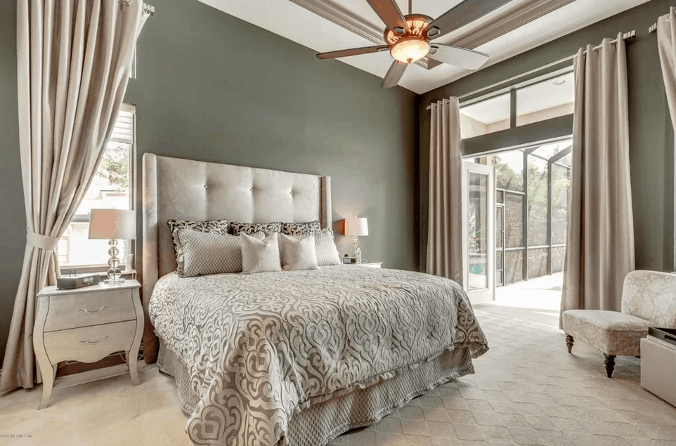 Traditional bedroom with gray walls and carpet flooring together with ceiling fan with flush light and tray ceiling.