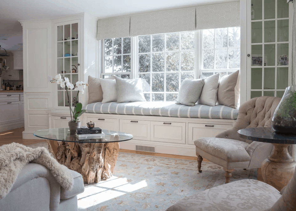 Traditional living room with built-in shelving and bench seating along with glass top tables and rug.