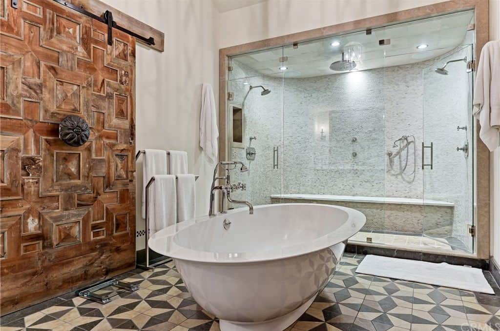 This primary bathroom features a stylish tiles flooring and a very charming wall decor. There's a large walk-in shower in front of the freestanding tub.