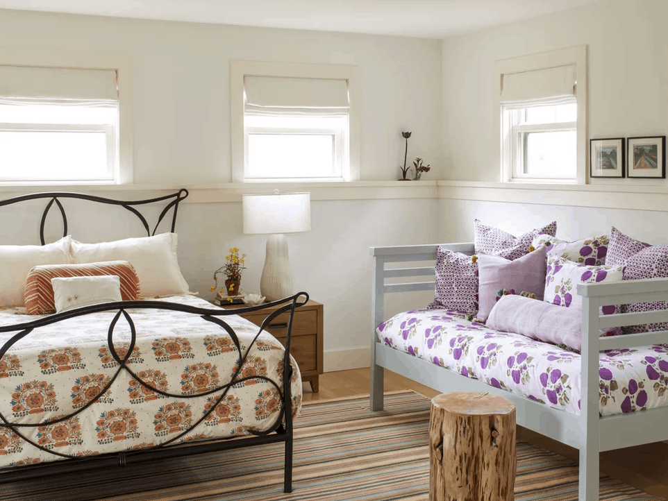 White bedroom with touches of grey, brown, violet, and black.