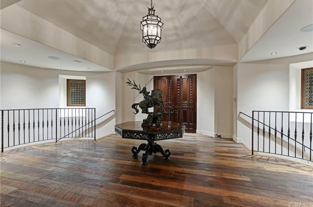 This bewitching foyer will make you experience a grand entrance featuring its statue on the center set on a hardwood flooring.