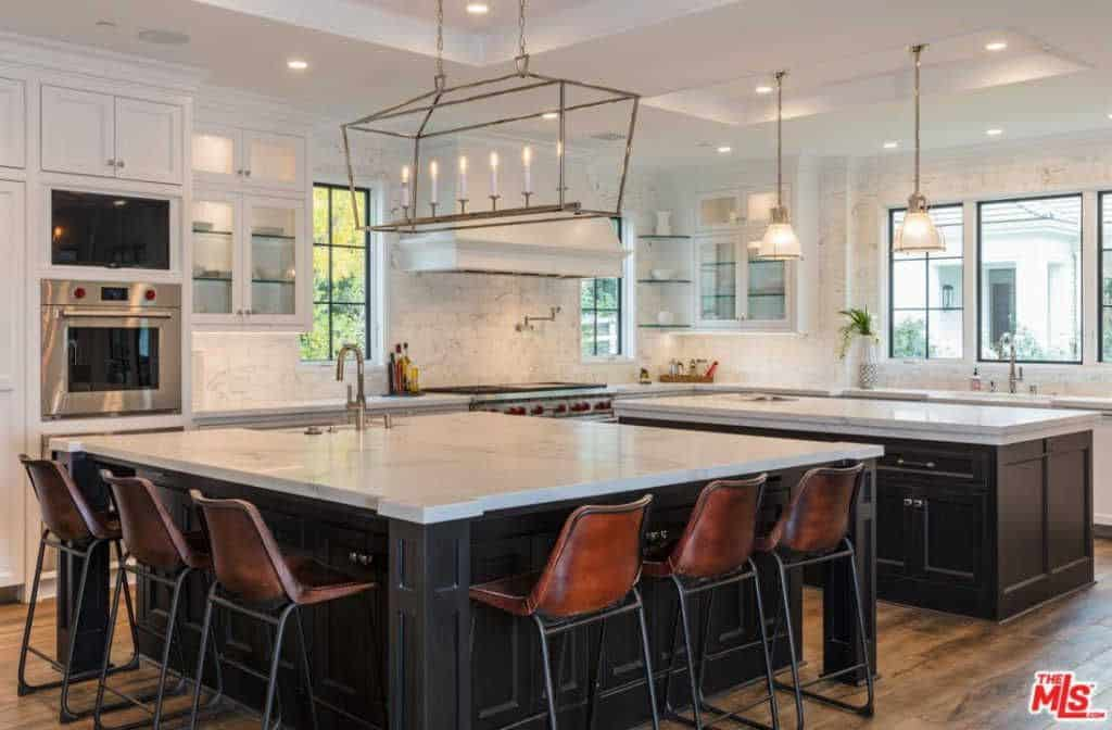 Huge dine-in kitchen with white marble walls and table top along with candle light chandelier and stainless steel appliances.