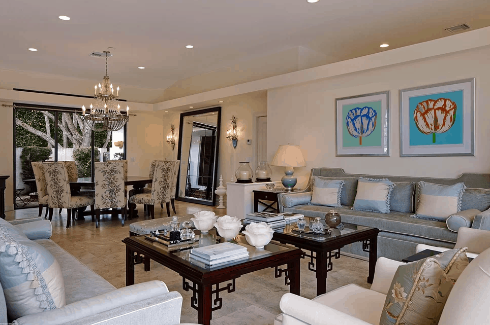This living room offers a luxurious sofa set with classy center tables set on the stylish flooring. The dining table is set on the side lighted by a glamorous chandelier and wall lighting.