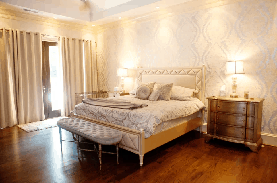 Glam bedroom with white walls and warm table lamp lighting together with hardwood flooring and recessed ceiling lights.