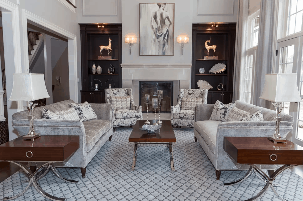 White glam living room with elegant table and lamp shade along with with rug and a fireplace.