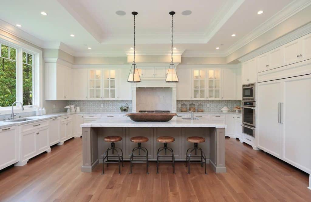 Large U-shaped kitchen featuring white cabinetry, counters and marble countertops along with a large center island set on the hardwood flooring lighted by pendant lights.