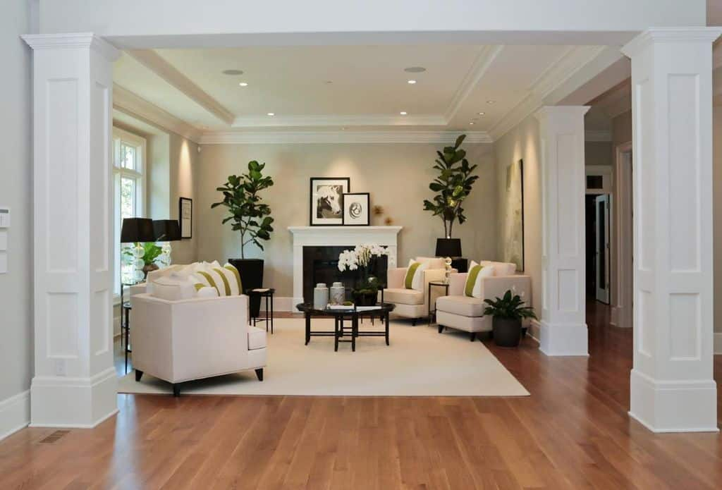 Elegant-looking white living room with a fireplace and a rug along with tray ceiling and recessed lights.