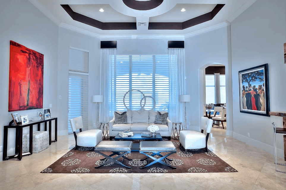 This living room boasts elegant wall decors and classy rug on top of the tiles flooring. The seats look magnificent together with the room's ceiling.