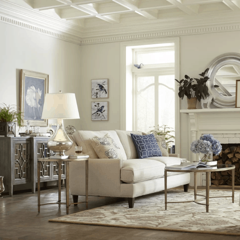 Traditional living room with white walls and coffered ceiling together with hardwood flooring and a fireplace.