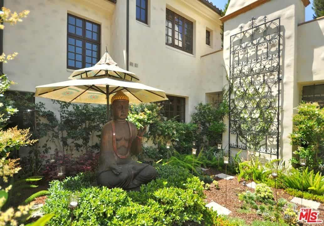 This garden with a statue adds elegance to the vintage look of the home.
