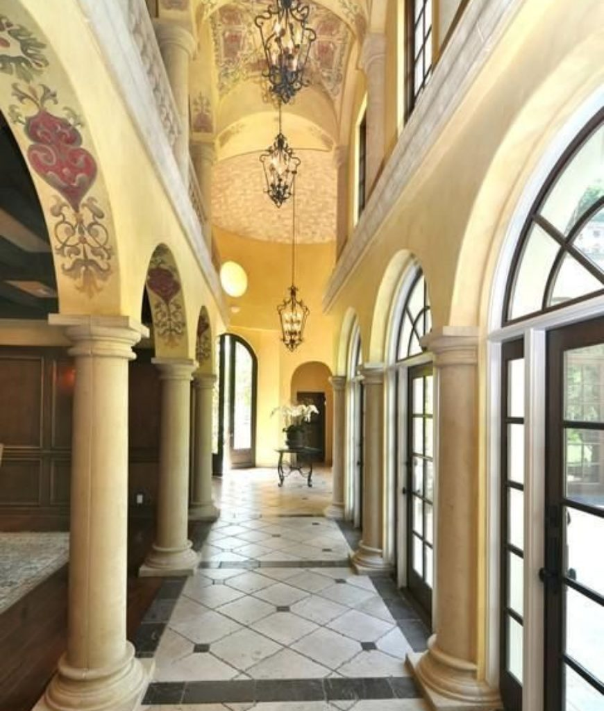 The hallway is full of groin vault ceiling with elegant pendant lights and stylish designs on it.