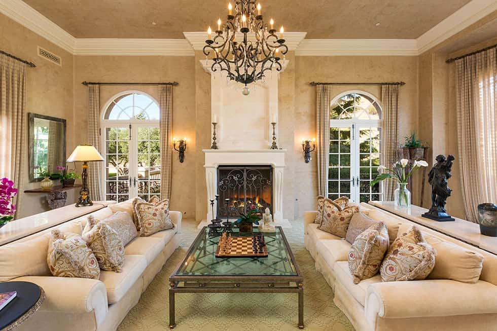 The formal living room is totally decked out with french doors, chandelier, fireplace, two facing traditional sofas and tray ceiling.
