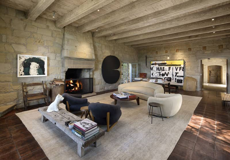 This luxury living room has awesome aged ceiling beams, stone wall and fireplace, tile flooring and very cool contemporary furniture that nicely juxtaposes the aged stonework and ceiling timbers.