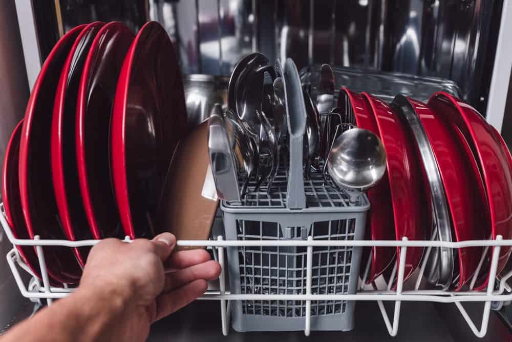 Open dishwasher with clean plates and utensils