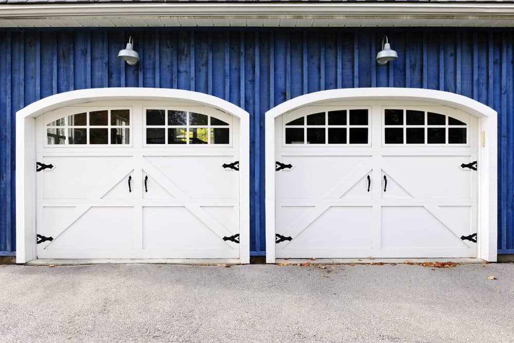 Striking white carriage style garage doors on blue home.