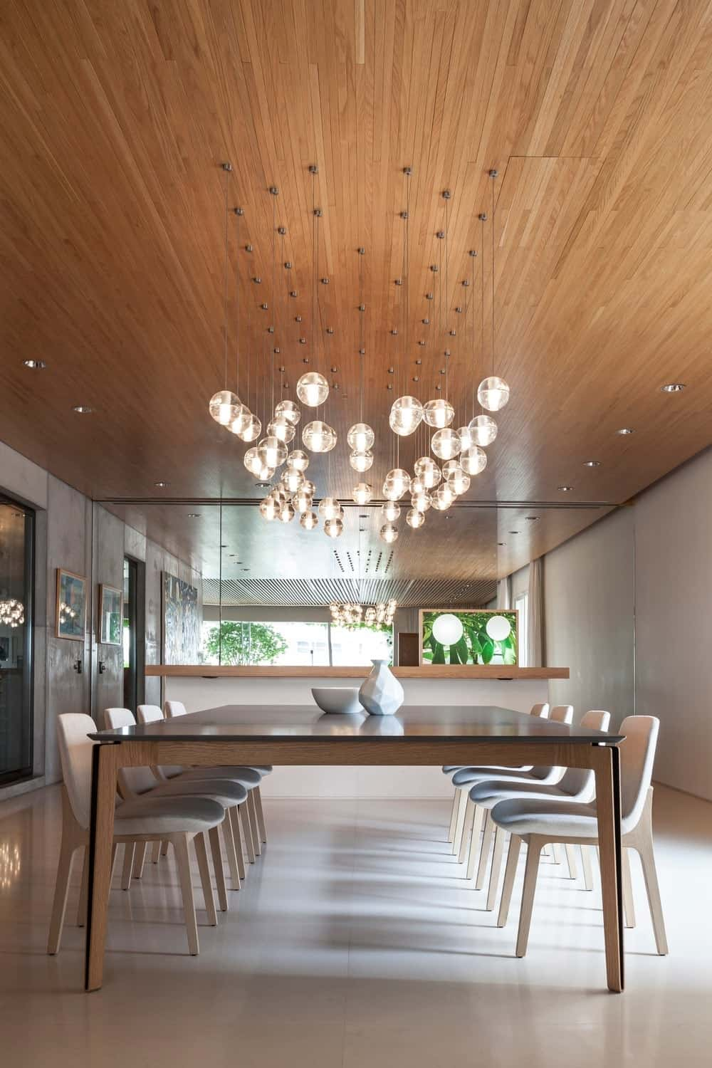 Dining room with huge 8-seat rectangular table lighted by beautiful pendant lights. Photo Credit: RuiTeixeira