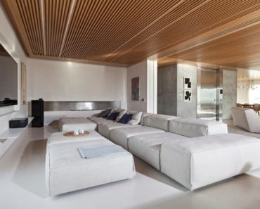 Family room with white walls and TV on wall together with a long sofa. Photo Credit: RuiTeixeira