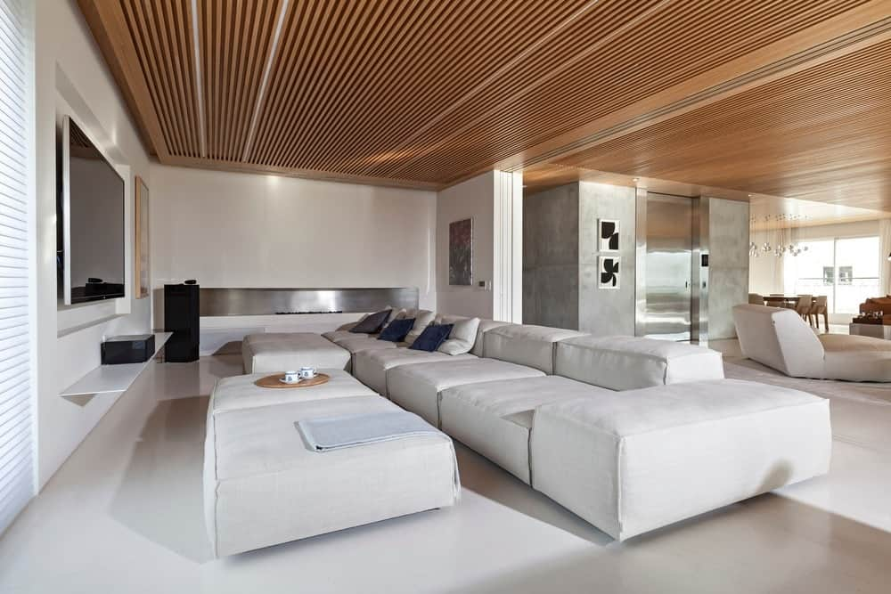 Large media room with white walls and floors matching the white sofa set under the stylish wooden ceiling.