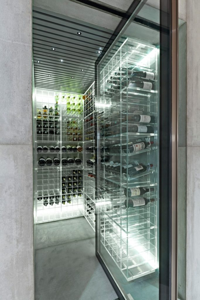 Sleek wine cellar with metal wine rack illuminated by recessed lighting along with a glass door and concrete floor.