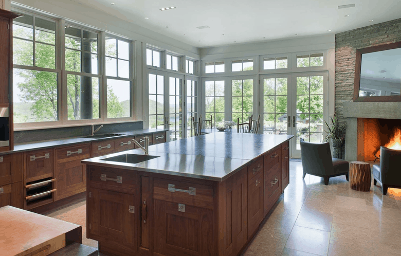 Large kitchen island in kitchen with floor-to-ceiling windows.