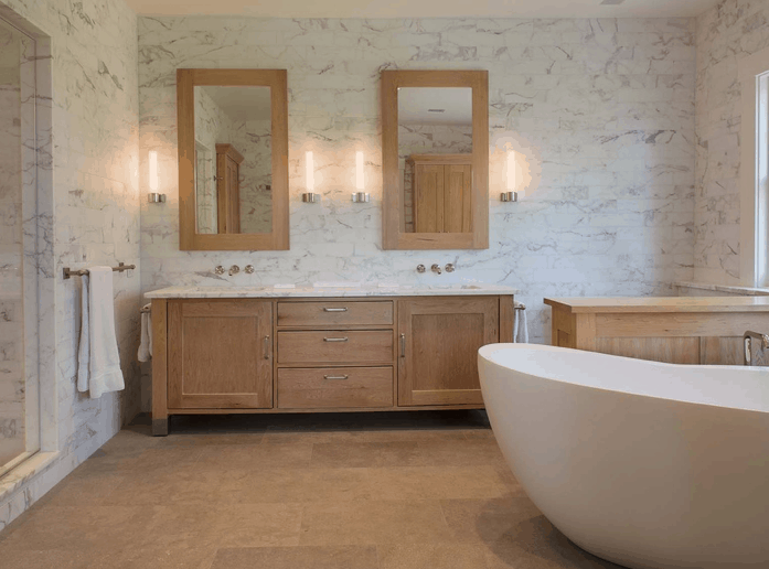 Large primary bathroom with freestanding white tub and double sink vanity