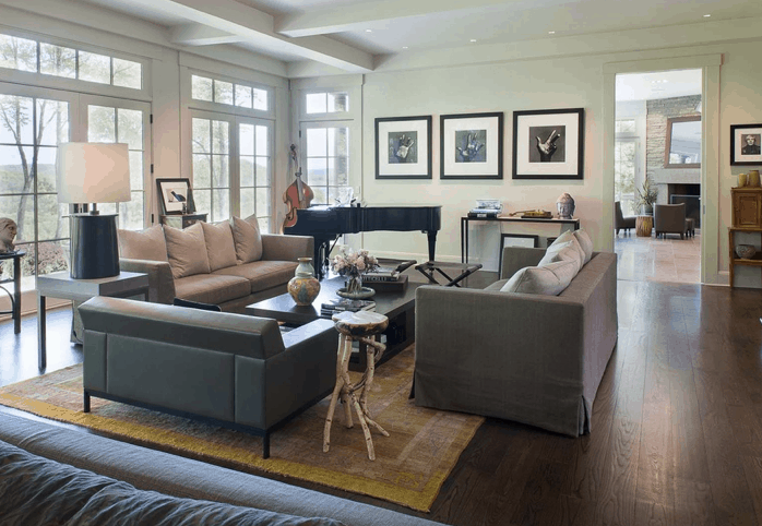 A formal living room with comfy seats set on the hardwood flooring covered by a rug. The walls and ceiling look perfect together.