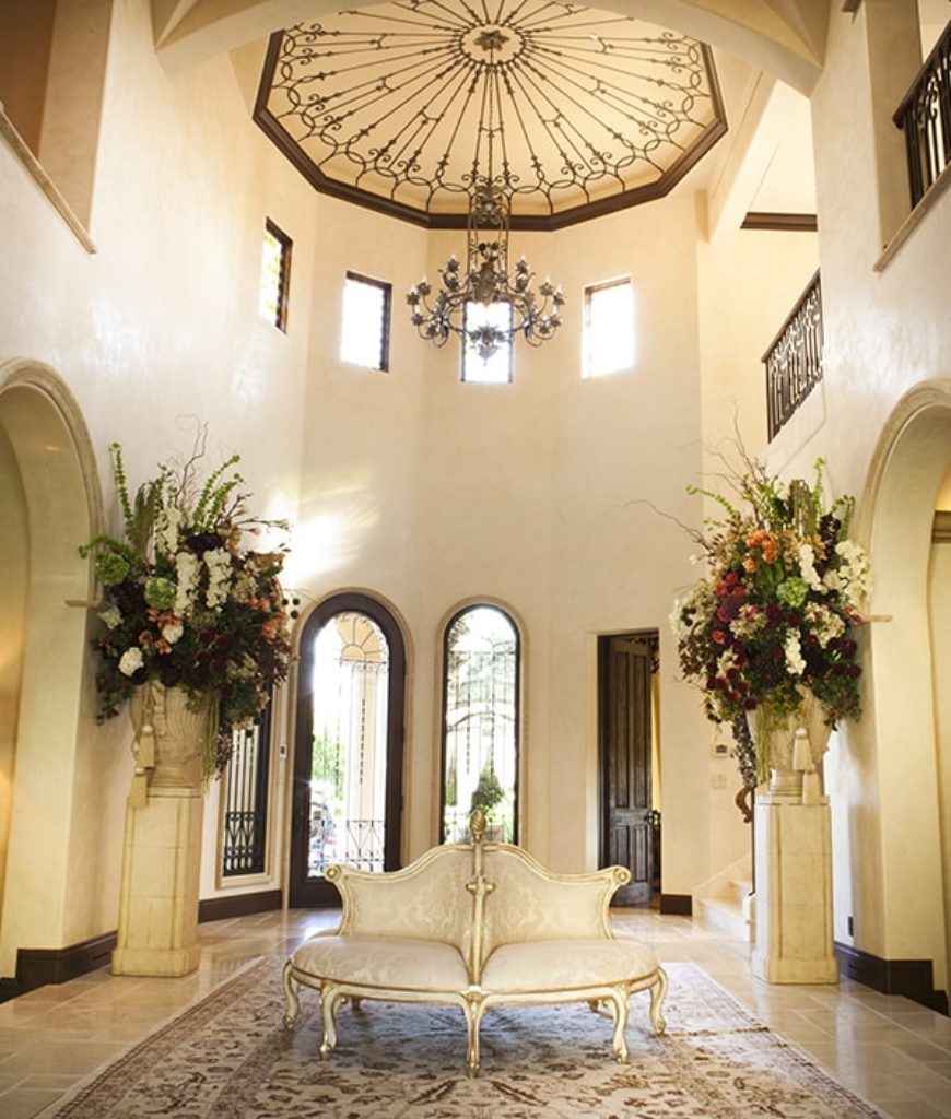 The entryway offers a grand entrance boasting a high cathedral-style ceiling with chandelier and sitting area on the middle.