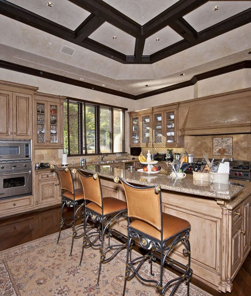 The kitchen boasts a dome ceiling and hardwood flooring. The room also offers a breakfast bar with marble countertop.