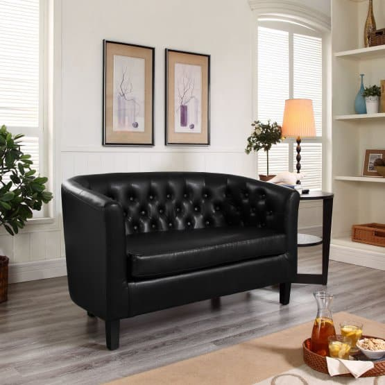 Black loveseat with a rubberwood frame and a button-tufted faux leather upholstery.