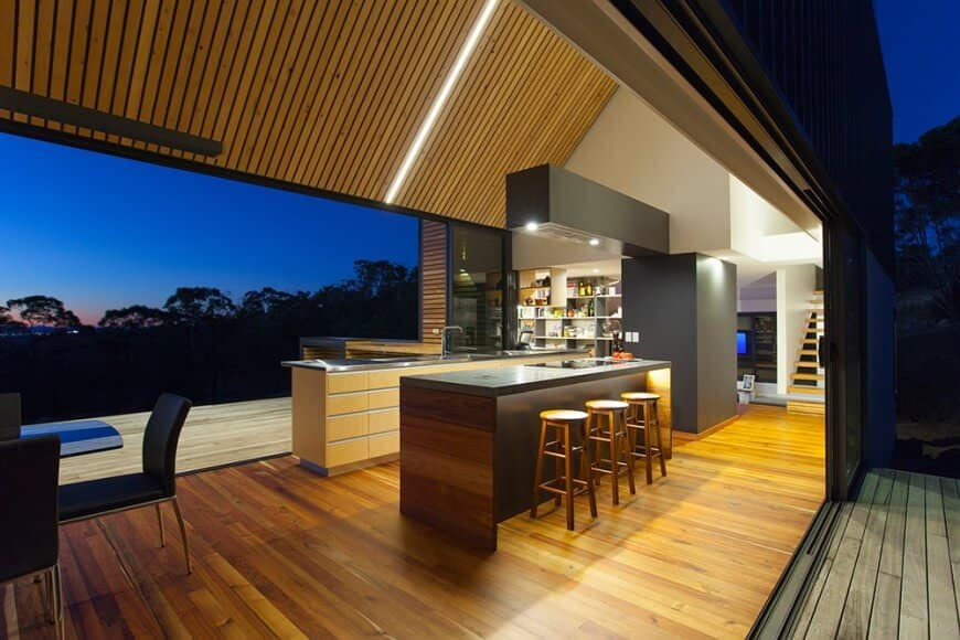 Black kitchen with wooden ceiling and floors.