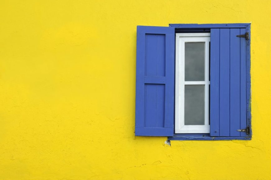 Blue exterior shutters against yellow wall.