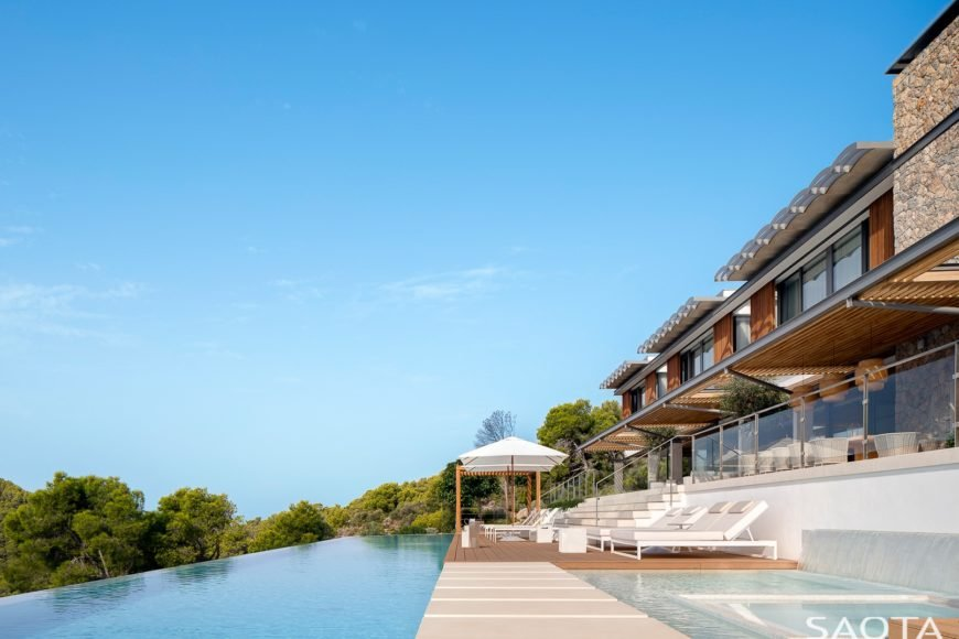 This resort-like home boasts a large infinity pool and multiple lounging spaces overlooking the stunning surroundings.