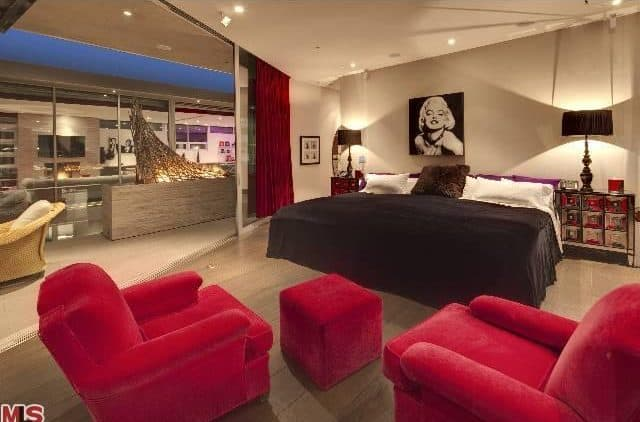 The bedroom boasts a couple of red velvet club reclining chairs matches by an ottoman. The king sized bed features two end table topped by a couple of table lamps. Wide glass sliding door leads to outdoor space.