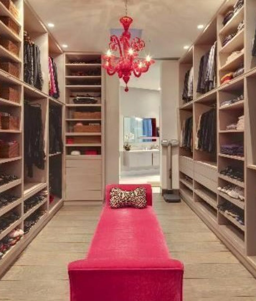 The closet offers a velvet-finished seating with hardwood flooring lighted by chandelier and recessed lights.