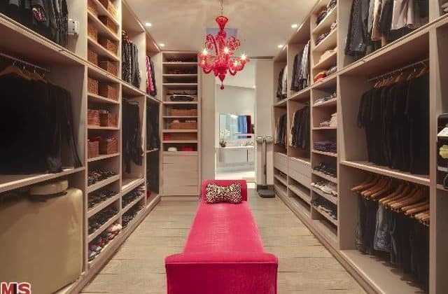 This bedroom closet features a red chandelier matching the red bench seating set on a hardwood flooring.