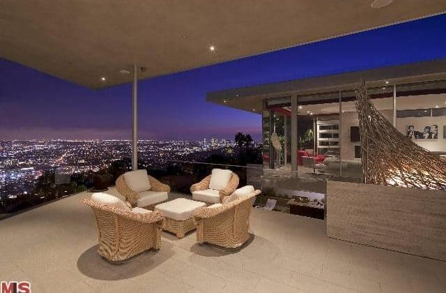 Luxurious patio set overlooking the bright lights of the city during night time.