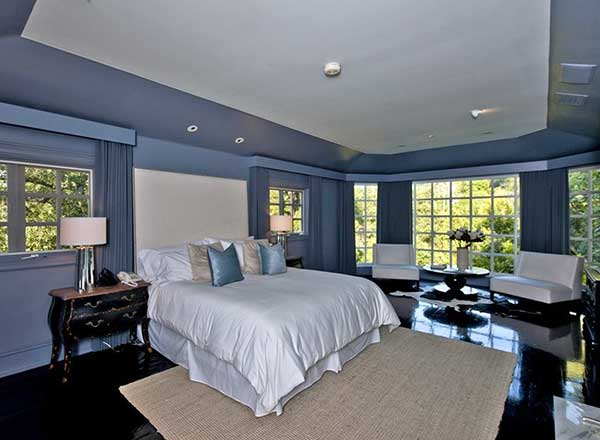 The blue themed master suite features a dark hardwood flooring and glass windows.