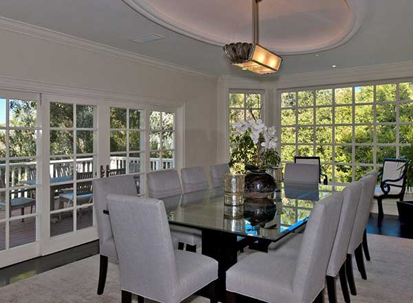 The dining room boasts an elegant look featuring a cove ceiling with a nice pendant lighting. Contemporary chairs matches well with the glass rectangular table while glass doors lead to the patio.