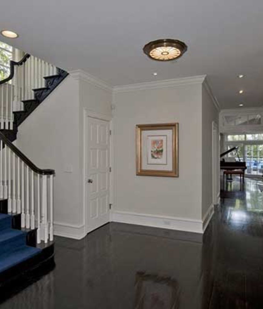 The foyer features a dark hardwood flooring with a curved staircase lighted by recessed and flush lights.