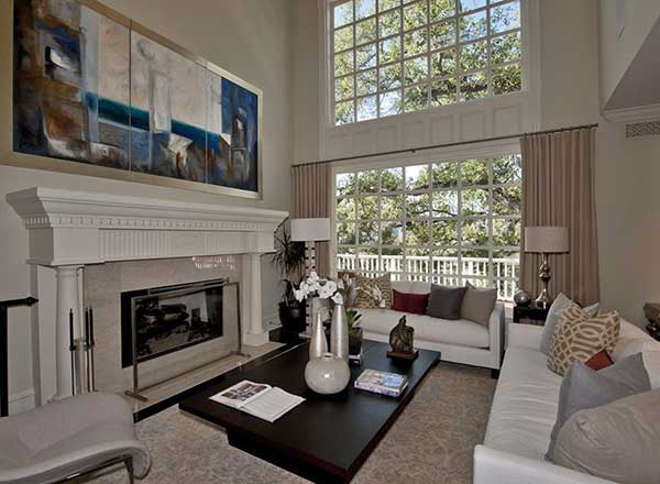 The living room looks elegant boasting a high ceiling and glass windows. The sofa set perfectly placed in front of the fireplace.
