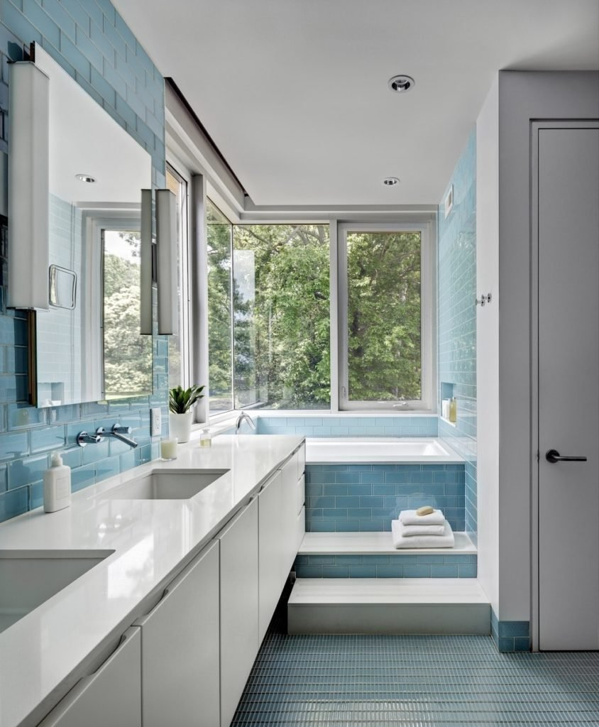 Master bathroom featuring stylish blue tiles walls and flooring along with a double sink and corner tub by the windows.