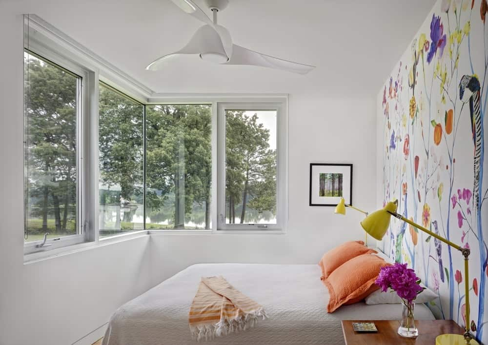 Bedroom featuring glass windows and white walls with a wall paint art. Photo Credit: Francis Dzikowski/OTTO