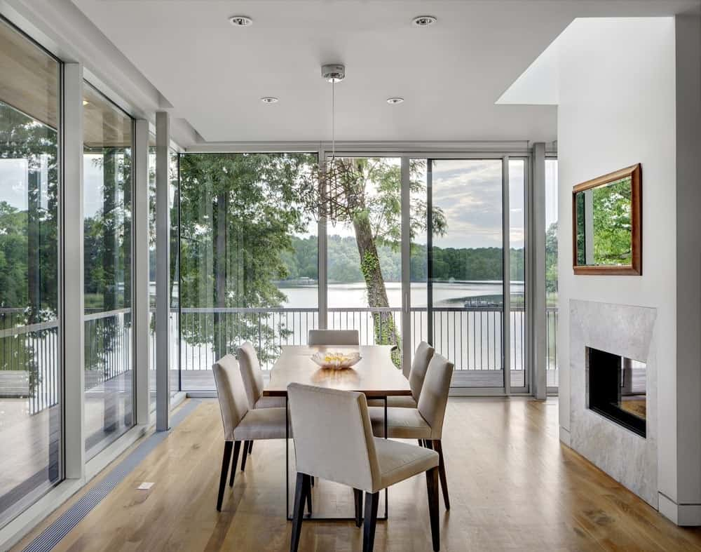 Modern dining room with a wooden dining table and beige upholstered chairs surrounded with panoramic windows overlooking a scenic outdoor view.