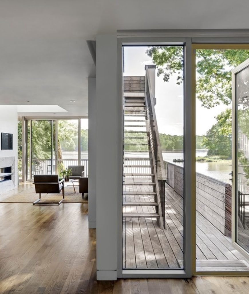 The entry to the house from the deck features a glass door and hardwood flooring. Photo Credit: Francis Dzikowski/OTTO