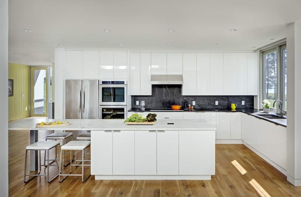 Modern kitchen filled with white island bar and sleek glossy cabinetry contrasted with black marble backsplash tiles.