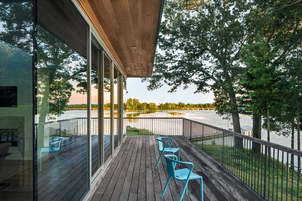 This traditional deck on a modish house overlooks the beautiful river and the greenery surrounding the house.