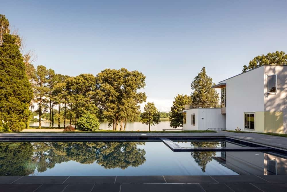 This lake-side home boasts an outdoor pool surrounded by tall trees.